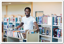 A young black man with a book truck in a library.