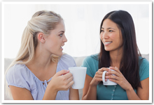 Two women chatting over coffee.