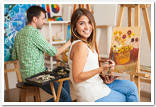A happy young woman and a man attending a painting workshop together and having fun.