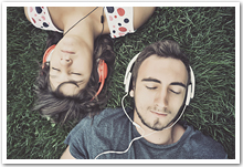 A couple lying in the grass listening to music with headphones on.