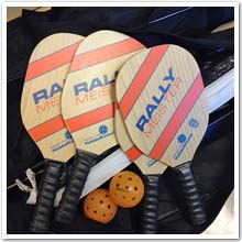 Pickleball raquets, balls and a net.