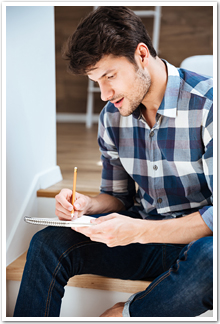 A young man writing in a notebook.