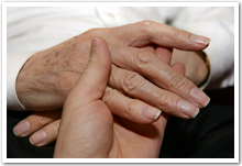 The hand of an elderly person being held by a hand of a younger person.