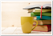 A stack of colourful books beside a yellow coffee mug.