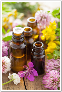 Four vials of essential oils surrounded by colourful herbs.