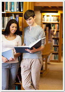 A female and a male student reading a book in a library.