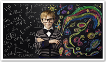 A boy standing in front of a blackboard with math equations & drawings