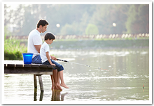 A father and son fishing off the end of a dock.