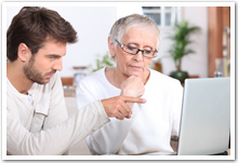 Man teaching senior woman with computer