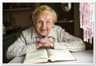 Elderly woman at a table, smiling towards the camera, with an open book in front of her.