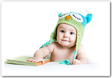 A happy baby wearing a knitted owl hat with his hand on a book.