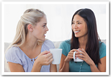 Two young women chatting over coffee.