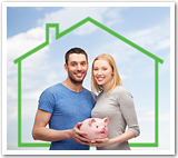 A young couple holding a piggy bank and standing in front of a house.