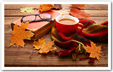 An old book with reading glasses, a cup of tea, a scarf & fall leaves.