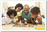 A happy family playing a board game on the floor.