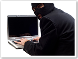 A masked man sitting at a computer.