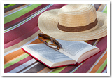A sunhat, sunglasses and a book on top of a beach blanket.