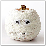 A pumpkin with two googly eyes and wrapped in gauze.