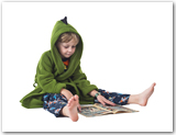 Young boy wearing pajamas and a hooded blanket reading a comic.