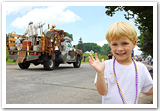 A young boy in front of a parade waving into the camera.