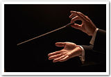 A conductor's hands against a black background.
