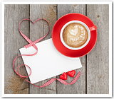 A white envelope, red gingham ribbon, candy hearts and a cappuccino.